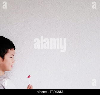 Side view of a smiling boy holding half eaten lollipop - Stock Photo