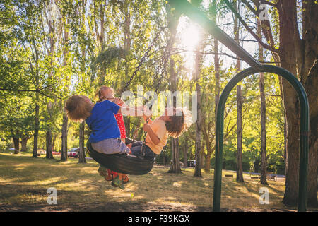 Three children playing on a swing - Stock Photo