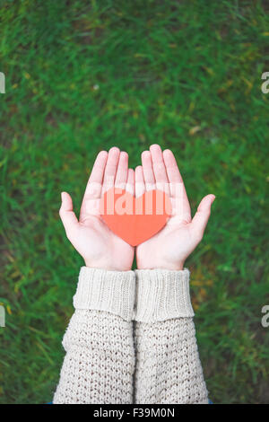 Woman holding a paper heart in her hands - Stock Photo