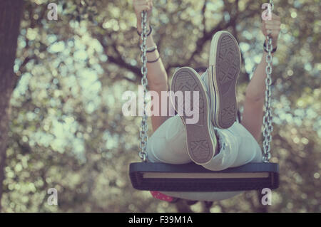 Low angle view of a teenage girl on a swing - Stock Photo