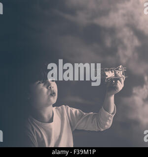 Portrait of a boy playing with toy plane - Stock Photo