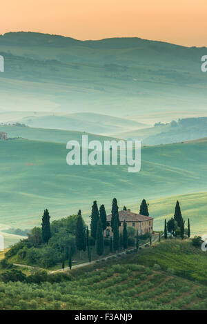 Tuscany, lonely farmhouse in the green and golden country hills of Val d'Orcia, early morning. Italian landscape. - Stock Photo