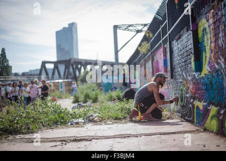 Male street artist creating a mural in London's east end, near Liverpool Street/Bethnal Green. - Stock Photo
