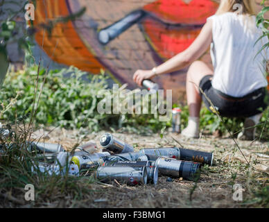 Female street artist creating a mural in London's east end, near Liverpool Street/Bethnal Green. - Stock Photo