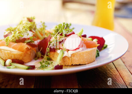 Close up fresh salad with  smoked salmon radish and beets outside on a wooden table - Stock Photo