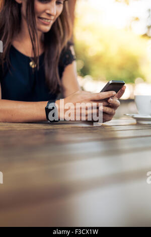 Cropped image of young woman using smart phone in a outdoor cafe. Female reading a text message on her mobile phone. - Stock Photo