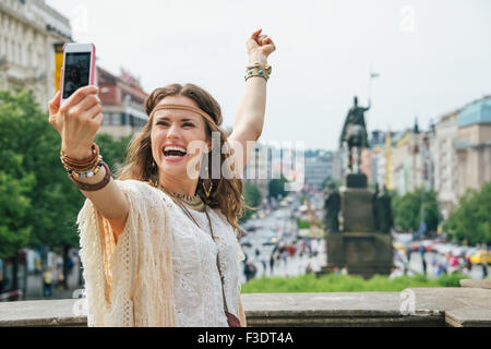 Happy young brunette bohemian woman tourist making selfie in the historical center of Prague. In the background - Stock Photo