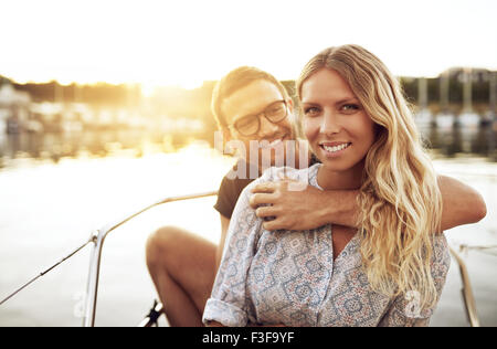 Young Couple In Love Sitting Outside on a Warm Summer Day - Stock Photo