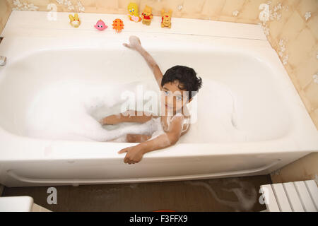 Boy taking bath in tub bath foam toys at side MR#468 - Stock Photo