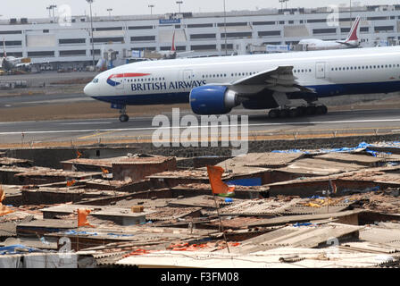 Commercial airliner preparing take off Sahar Airport Chatrapati Shivaji International Airport foreground slums airport - Stock Photo