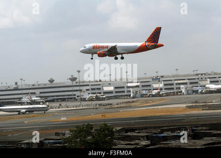 Airlines commercial airliner preparing land Sahar Airport Chatrapati Shivaji International foreground slums airport - Stock Photo