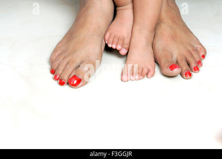 Feet foots legs of young baby child and adult woman mother legs comparison big and small - MR#152 - RMM 146939 - Stock Photo