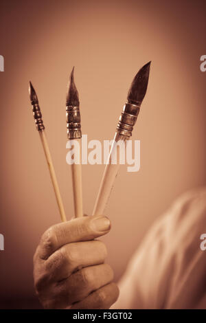 Painter's hand holding three paintbrushes - Stock Photo