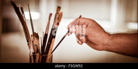 Painter's hand taking a brush in a pot - Stock Photo
