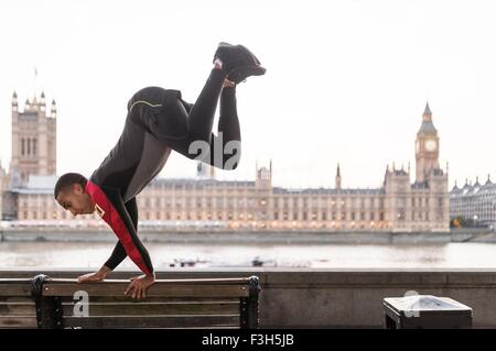 Young man leaping over park bench on Southbank, London, UK - Stock Photo