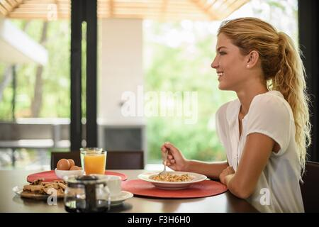 Young woman at breakfast table eating cereal - Stock Photo