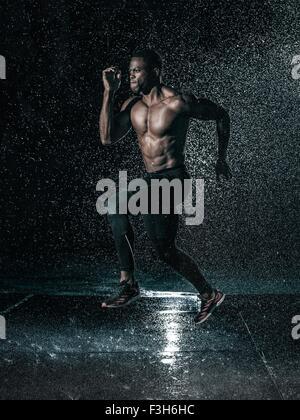 MId adult man, outdoors, running in rain - Stock Photo