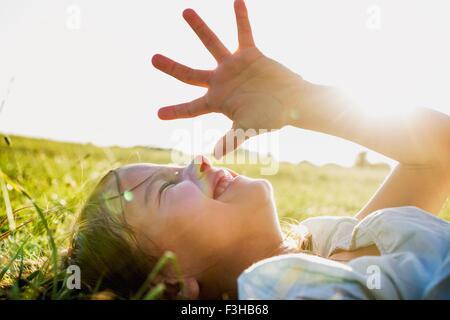 Girl lying in park shielding eyes from sunlight - Stock Photo