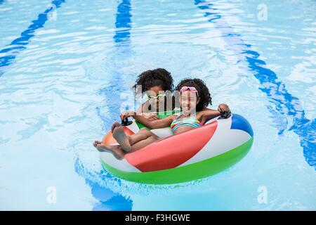 Girl in swimming costume playing with garden hose stock Silver ring tarnished in swimming pool