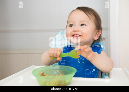 Baby boy eating baby food in kitchen high chair - Stock Photo
