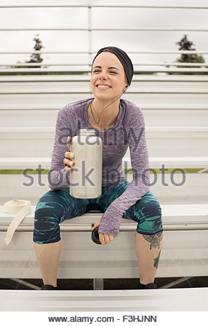 A young blonde woman resting and drinking water after exercising at running track on bench - Stock Photo