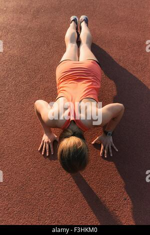 Young woman working out, doing press-ups, outdoors, elevated view - Stockfoto