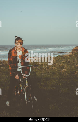 Teenage girl sitting on a bike by the coast - Stock Photo