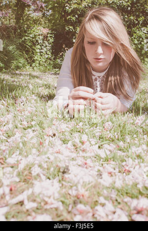 Young blond teenage girl in cherry blossom - Stock Photo