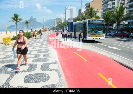 RIO DE JANEIRO, BRAZIL - APRIL 1, 2014: Bus stops along boardwalk bike path on Avenida Vieira Souto in Ipanema, - Stock Photo