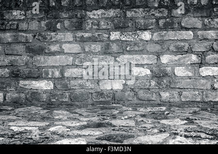 Old empty brick wall with stone floor, gray interior background. - Stock Photo