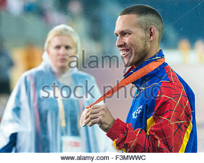Close up of Venezuelan athlete showing his medal at the 2015 Parapan American Games. A volunteer is seen wearing - Stock Photo