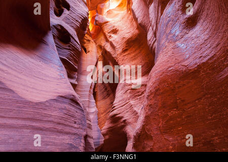 Colorful ancient sandstone walls eroded by time and water to create smooth layers in Canyon X in Page, Arizona. - Stock Photo