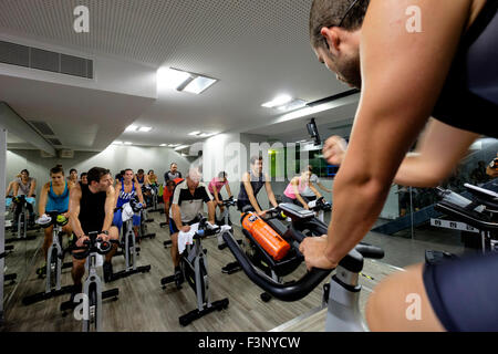 Fitness instructor encourages people riding stationary bicycles during a spinning class at the gym - Stockfoto