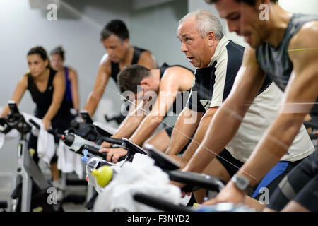 Side view of people riding stationary bicycles during a spinning class at the gym - Stockfoto