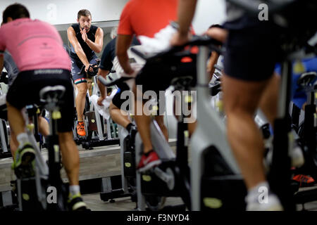 Fitness instructor in front of people riding stationary bicycles during a spinning class at the gym - Stockfoto