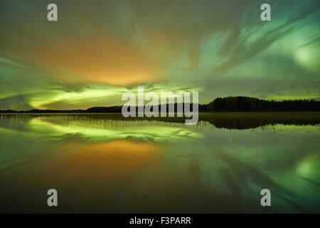 Northern lights (Aurora Borealis) above a lake with some clouds and reflections on the water at night. - Stock Photo