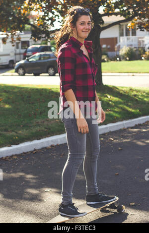 woman riding longboard skateboard at fall on daytime - Stock Photo