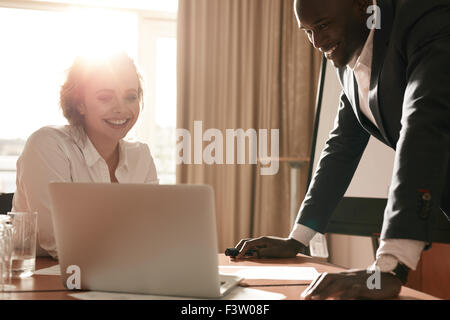 Portrait of happy young business team working together on laptop. Businessman and businesswoman meeting in conference - Stock Photo