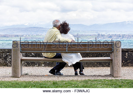 An elderly couple on a public bench watching the horizon. - Stockfoto