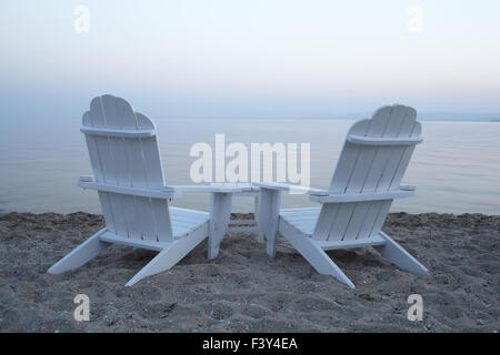 Empty wooden deck chairs on a beach - Stock Photo