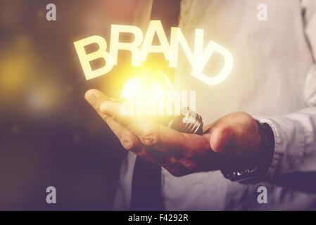 Brand idea concept with businessman holding light bulb, retro toned image, selective focus. - Stock Photo