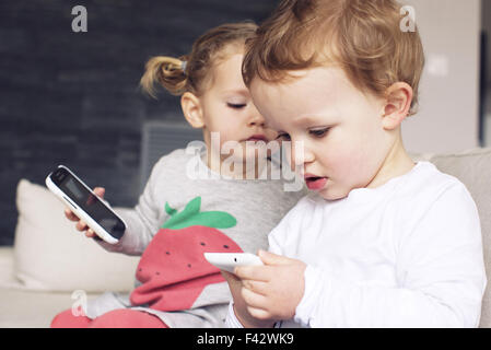 Children playing with smartphones - Stock Photo