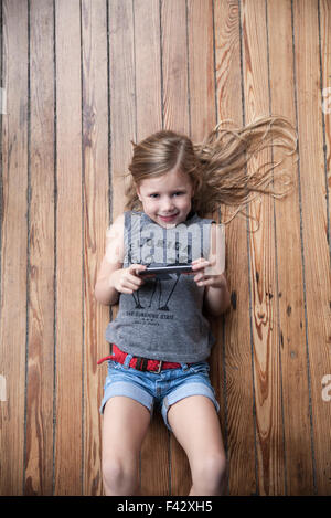 Little girl lying on floor using smartphone - Stock Photo