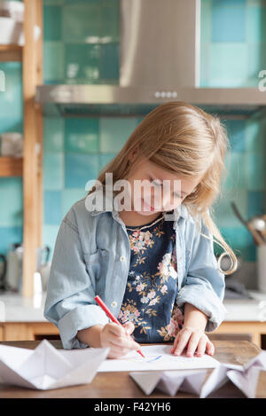 Little girl drawing in kitchen, portrait - Stock Photo