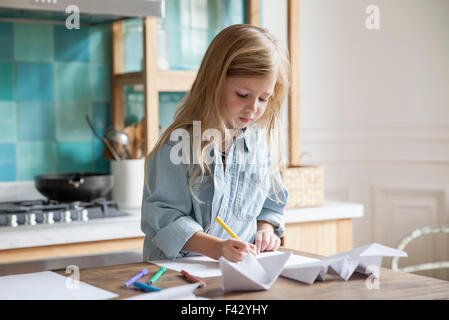 Little girl coloring in kitchen - Stock Photo