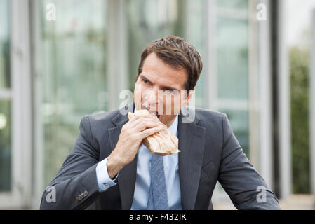 Businessman eating sandwich outdoors - Stock Photo