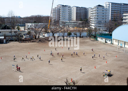 Children at play on dirt field school yard - Stock Photo