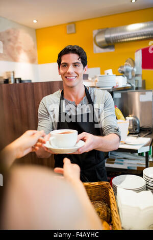 Waiter serving cappuccino to customer - Stock Photo