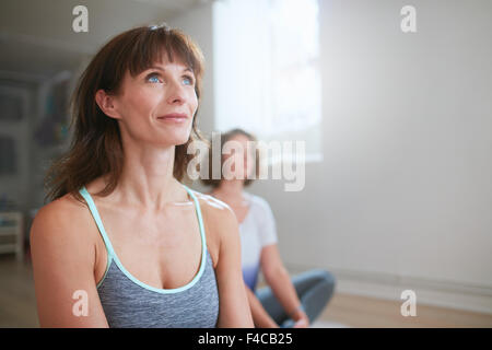 Portrait of fitness woman sitting on floor in yoga class looking away. Yoga trainer during workout  session in gym. - Stock Photo