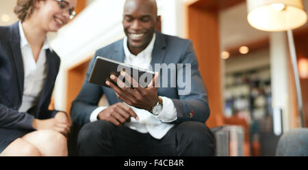 Happy young business people sitting together using digital tablet while at hotel lobby. Focus on tablet computer. - Stock Photo